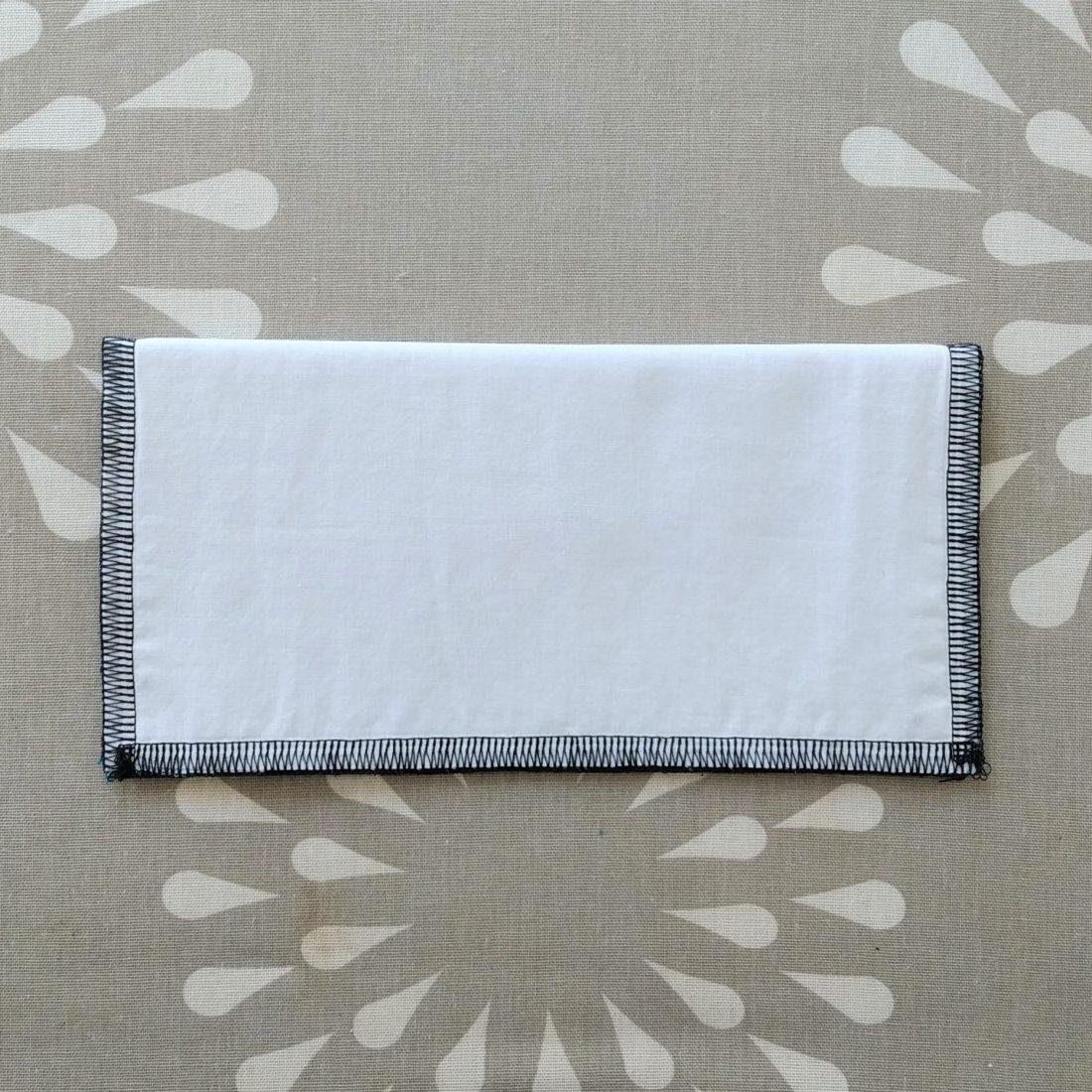 Pliez votre masque en deux puis repassez la pliure pour obtenir la moitié de votre carré.